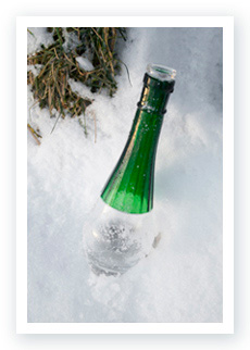A Flaska bottle with a green neck sitting in the snow