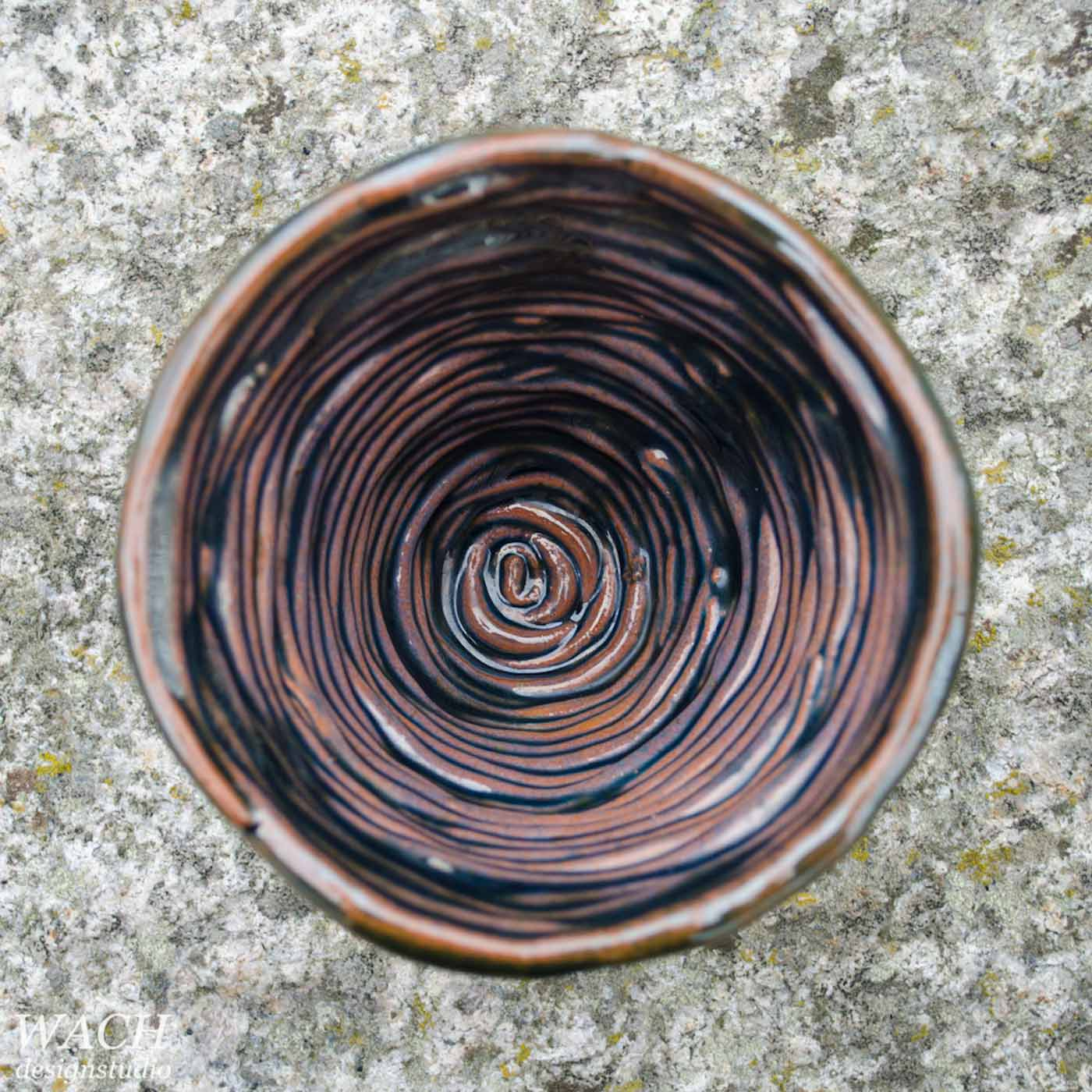 Coil Cup sitting on a stone