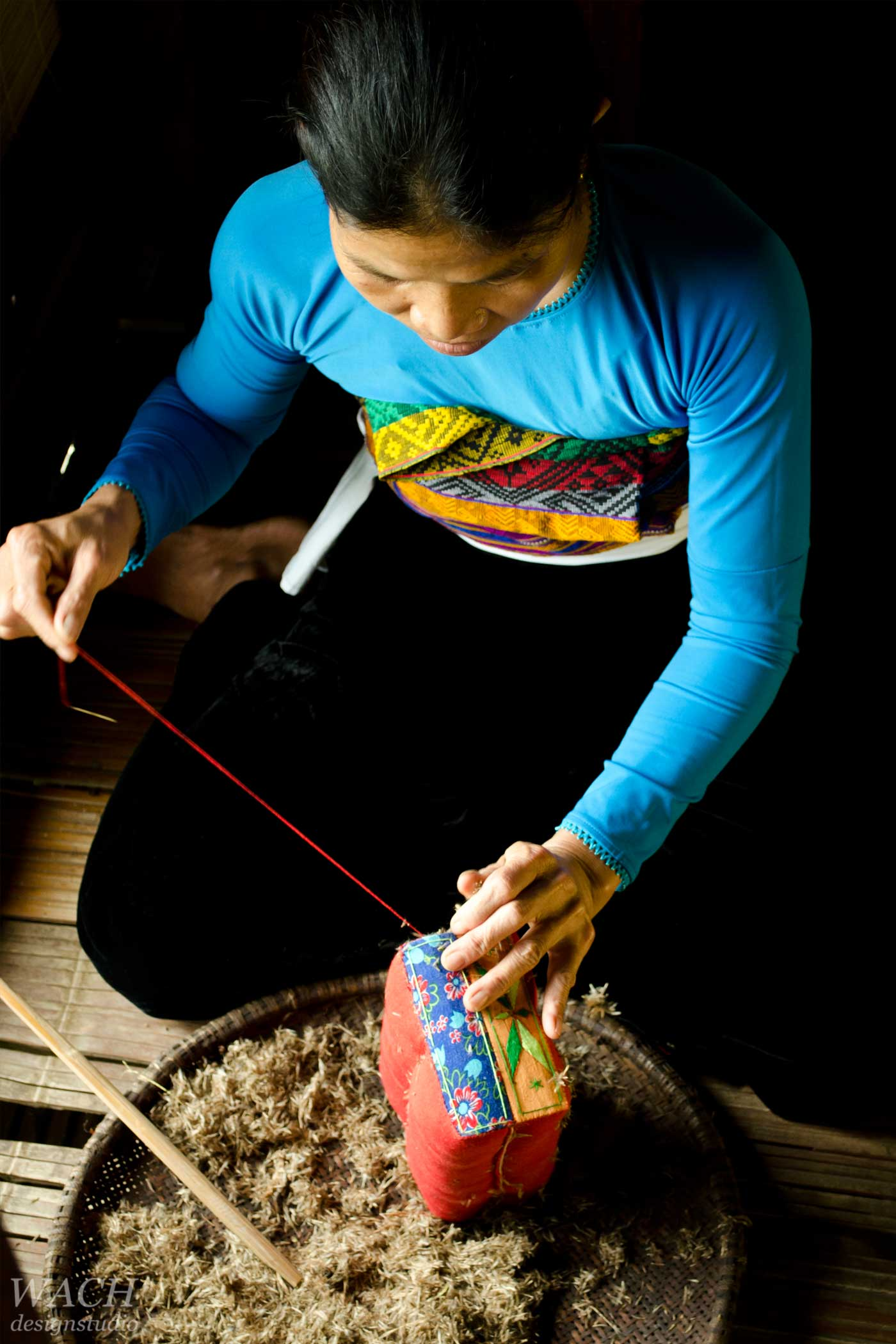 Vietnamese woman sewing traditional vietnamese cushion