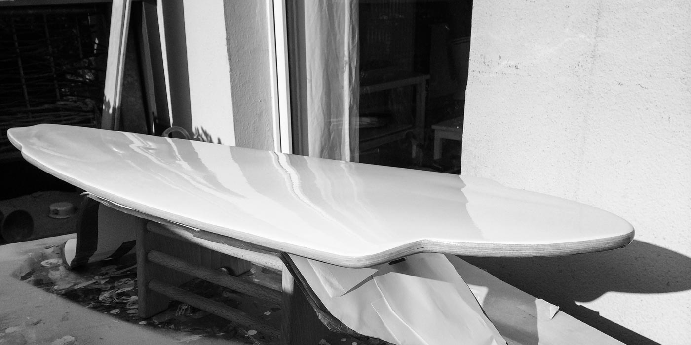Laying down yacht paint on the bottom of WACH designstudio longboard